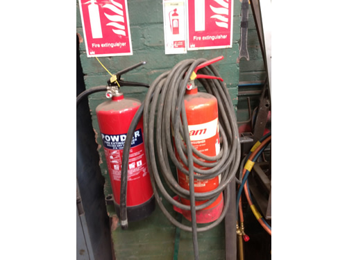 Fire extinguisher blocked by hose